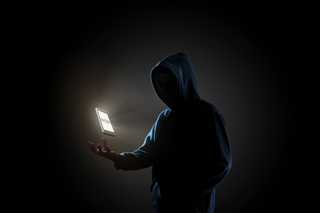 White smartphone with text HACKER on screen floating above of hackers hand in dark background. Finance, business, e-commerce or cyber crime concept Stock Photo