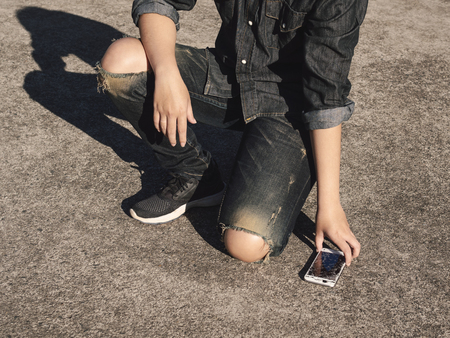 Young man picking broken and cracked screen smartphon from floor after dropped. Concept of broken or accident mobile phone, repair, warranty and technology