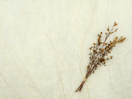 Top view bouquet of dried and wilted brown Gypsophila flowers on matt marble background with copy space