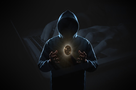 Golden Bitcoin floating above of hacker's hand in dark on hacker hacking with computer laptop background. Finance, business, e-commerce or cyber crime concept