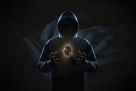 Goldenes Bitcoin schwebt über der Hand des Hackers im Dunkeln auf Hacker-Hacking mit Computer-Laptop-Hintergrund. Finanz-, Geschäfts-, E-Commerce- oder Cyber-Kriminalität-Konzept