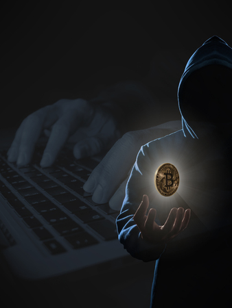 Golden Bitcoin floating above of hackers hand in dark on hacker hacking with computer laptop background. Finance, business, e-commerce or cyber crime concept Stock Photo