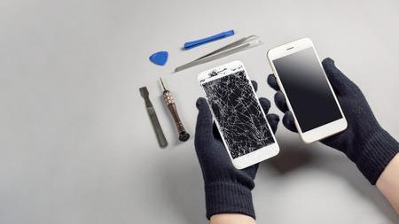 Técnico o ingeniero que se prepara para reparar y reemplazar la nueva pantalla del teléfono inteligente con pantalla rota y agrietada que se prepara en el escritorio con espacio de copia