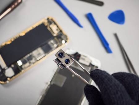 Technician or engineer showing broken dual smartphone camera on blurred smartphone components background Stock Photo