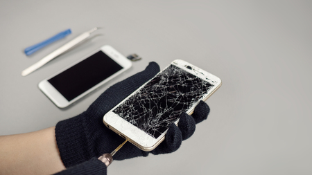 Technician or engineer opening broken smartphone for repair or replace new part on desk with copy space Stock Photo