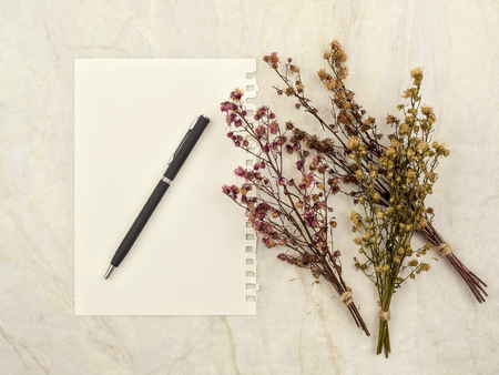 Top view of note pad paper with pen and group of bouquet dried and wilted multiple color Gypsophila flowers on matt marble background for text, letter, message or verse