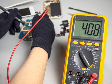 Technician or engineer using digital multimeter to electric current measurement on smartphone logic board for diagnosis broken smartphone Éditoriale