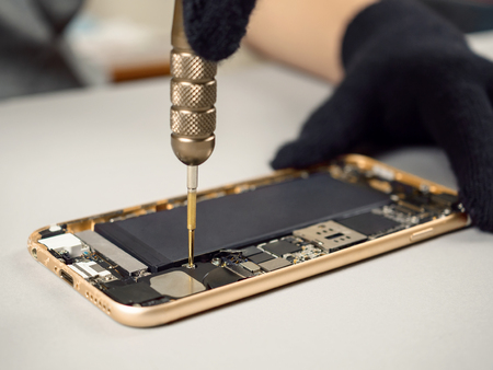 Technician or engineer disassembling components broken smartphone for repair or replace new part on desk