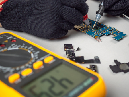 Technician or engineer using digital multimeter to electric current measurement on smartphone logic board for diagnosis broken smartphone Editöryel