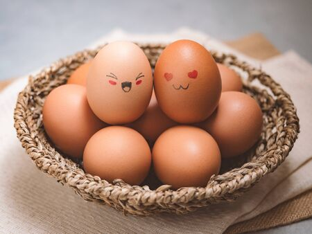 Egg lovers have happy faces of men and women on the pile of eggs in the basket. Organic egg food ingredients, Couples, Easter, Valentines day concept.