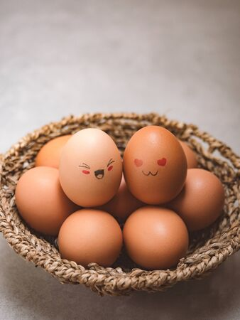 Egg lovers have happy faces of men and women on the pile of eggs in the basket with copy space. Organic egg food ingredients, Couples, Easter, Valentines day concept.