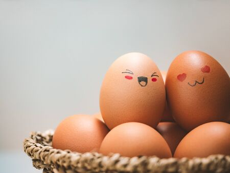 Egg lovers have happy faces of men and women on the pile of eggs in the basket with copy space. Organic egg food ingredients, Couples, Easter, Valentine's day concept. Stock Photo - 137482911