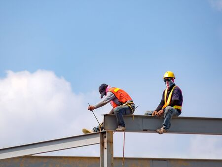 Two builders welding steel on high-rise steel frame without safety belt on construction site with blue sky background. Construction industrial. Copy space.