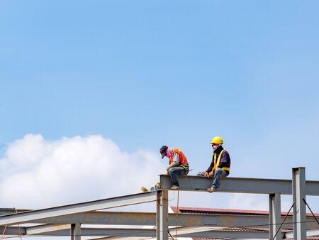 Due costruttori che saldano l'acciaio su un grattacielo in acciaio senza cintura di sicurezza in cantiere con sfondo blu del cielo. Edilizia industriale. Copia spazio.