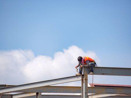 Costruttore di acciaio per saldatura su struttura in acciaio a molti piani senza cintura di sicurezza in cantiere con sfondo blu cielo. Edilizia industriale. Copia spazio.