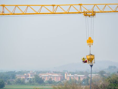 Construction workers were hung with cranes to control machines for pouring cement with security risks. 免版税图像