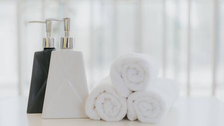 Shampoo and shower cream bottle with laundry white towel in bathroom with copy space.