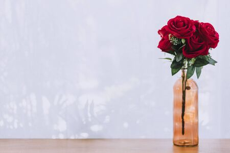 Red rose bouquet in bottle vase on wooden table with white curtain background with copy space. Valentine's day or wedding flower concept.