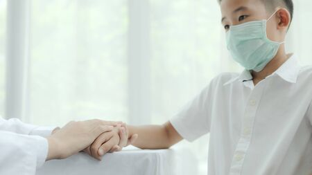 The doctor encouraging kid patient and wearing surgical mask for health care from Coronavirus (COVID-19). Health care and prevent from risk of Coronavirus (COVID-19) concept.