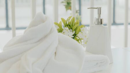 Shampoo and shower cream bottle with laundry white towel in bathroom.
