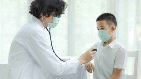 The doctor diagnosing disease for kid patient and wearing surgical mask for health care from Coronavirus (COVID-19). Health care and prevent from risk of Coronavirus (COVID-19) concept.