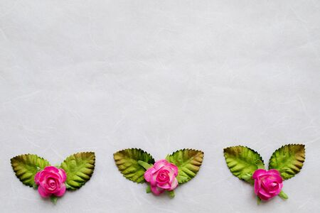 Pink artificial flower  on mulberry paper background photo