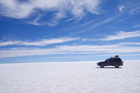 salt flat: Vehicle in a large salt flat in uyuni, bolivia Stock Photo
