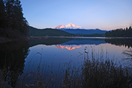 a reflection of mount shasta over a lake during sunset Stok Fotoğraf