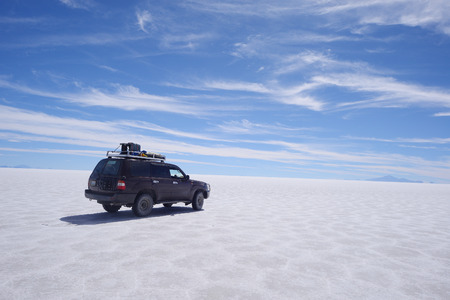 jeep travel in a large salt flat in uyuni, bolivia