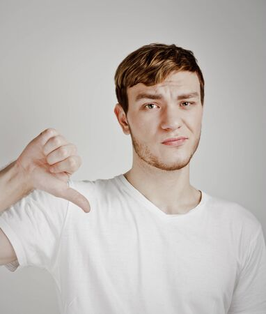 office politics: young man shows thumb down