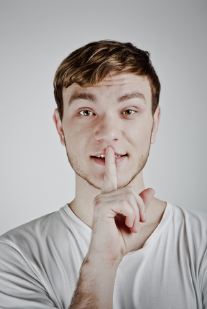 Young man with his finger over his mouth photo