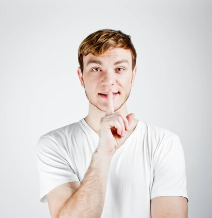 finger on lips: Young man with his finger over his mouth
