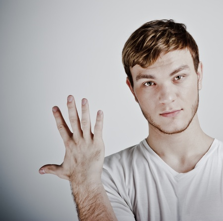 five fingers: young  man holding up five fingers