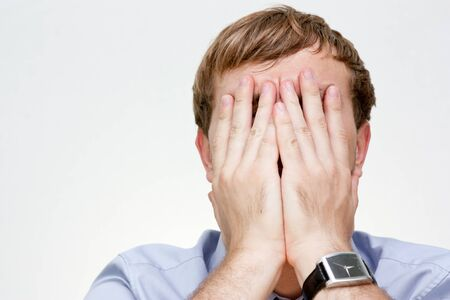 Portrait of a businessman covering the face with his hands photo