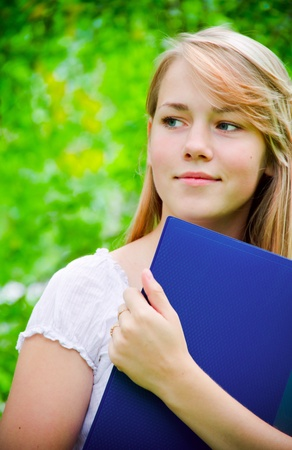 beautiful girl in the park with books photo