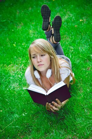 beautiful girl lying in the park with a book photo