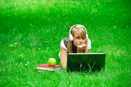 girl with laptop in the park listening to music photo