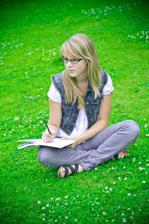 beautiful girl in the park reading a book photo