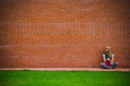 lezing: mooi meisje op een bakstenen muur Stockfoto