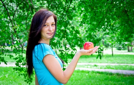 Cute young female holding an apple outdoors photo