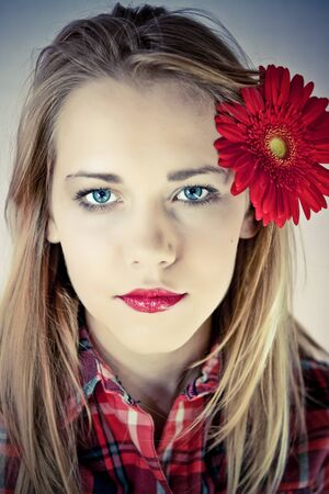 portrait of young beautiful woman with red flower in her hair photo