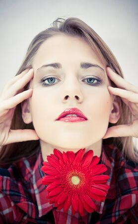 Beautiful portrait of a young sexy woman with bright red flowers. photo