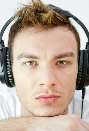 portrait of young man with headphones listening to music on a white background photo