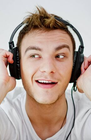 Young man wearing headphones and holding arms on them. photo