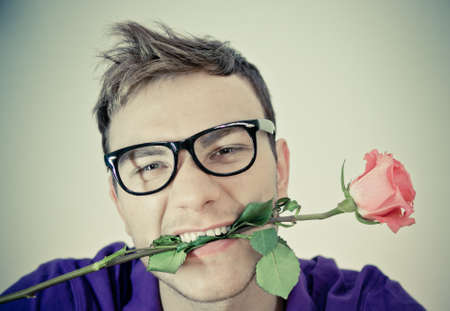 Young man holding  rose in his mouth photo