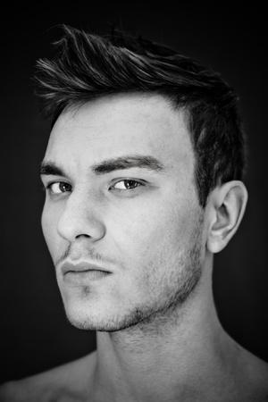 tatouage sexy: Portrait d'un beau jeune homme sur fond noir Banque d'images