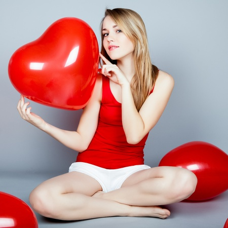 Valentines day woman holding red heart balloon photo