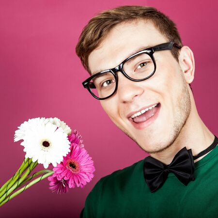 constraining: Young smiling man holding a bouquet of flowers