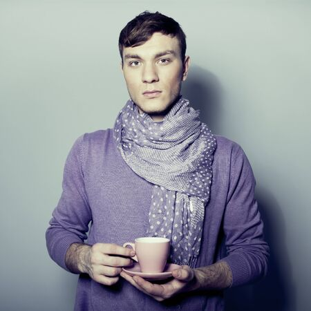 Young man with cup of coffee in his hands Stock Photo - 12390430