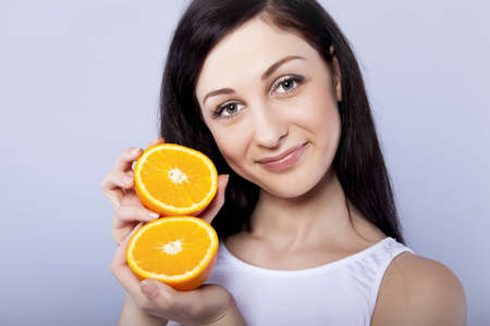 Young happy girl with orange in her hands Stock Photo - 12535936